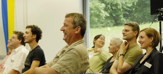 Menschen lachen auf einer Veranstaltung- Mehr Demokratie - Arbeitskreise